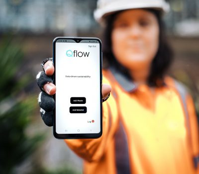 Qflow smartphone app held by construction worker